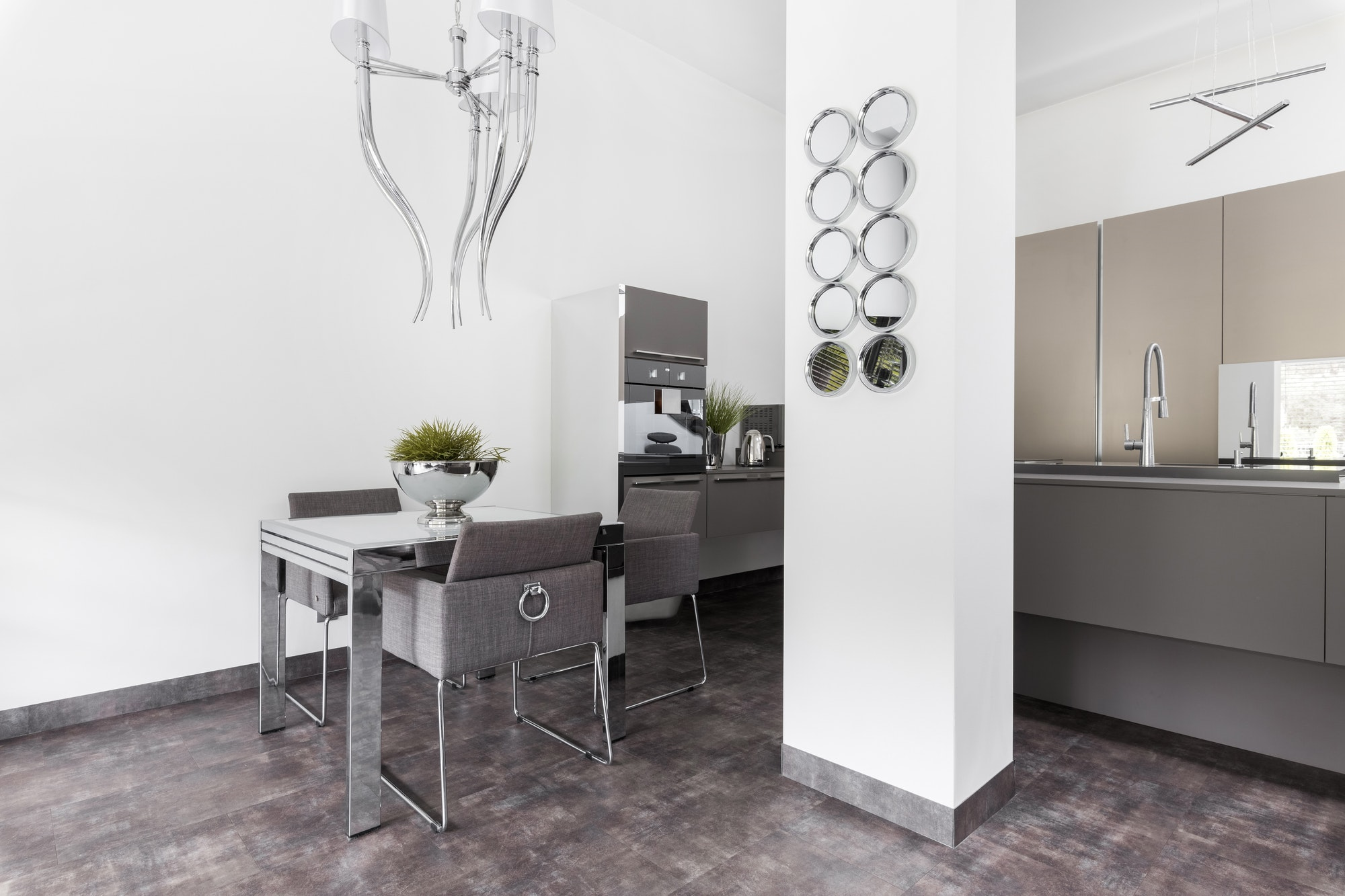 Elegant kitchen with dining room table and grey design in fashionable house